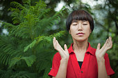 Beautiful Asian girl doing deep breathing exercise in nature.