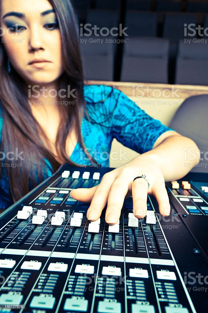 Beautiful Asian Girl in 20s at a Recording/Sound Console royalty-free stock photo