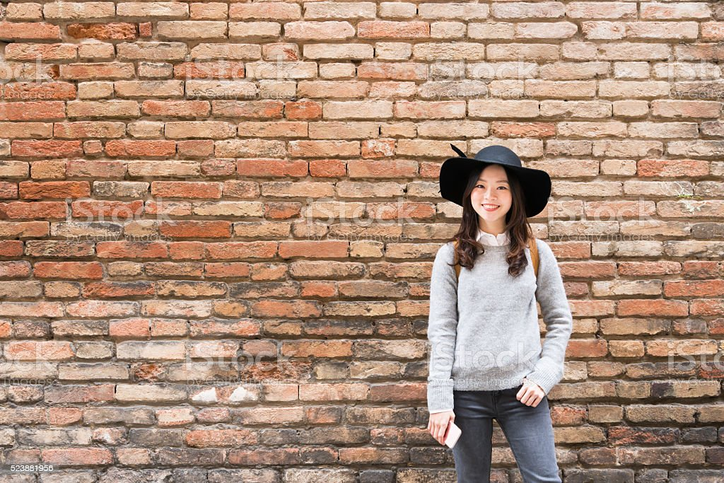 Beautiful asian girl smiling, copy space on brick wall background stock photo
