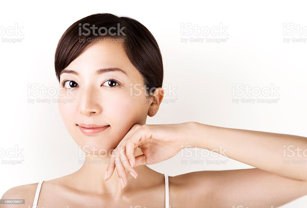 Beautiful asian girl touching her face isolated on white stock photo