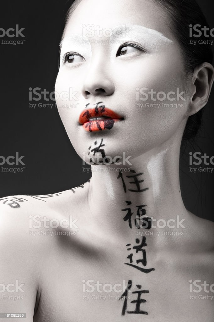 Beautiful Asian girl with white skin, red lips and hieroglyphics stock photo