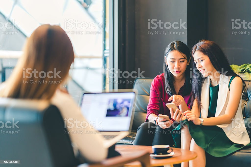 Beautiful Asian girls using smartphone and laptop at cafe stock photo
