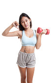 Beautiful Asian healthy girl thumbs down with dumbbell.