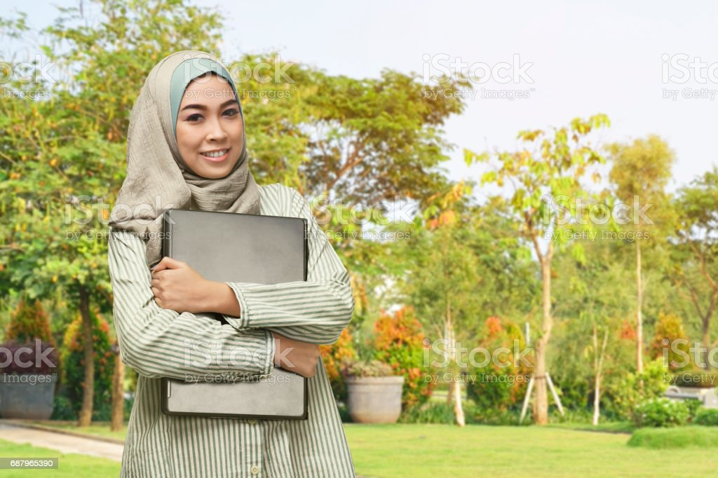 Beautiful asian muslim woman with smiley face holding laptop stock photo