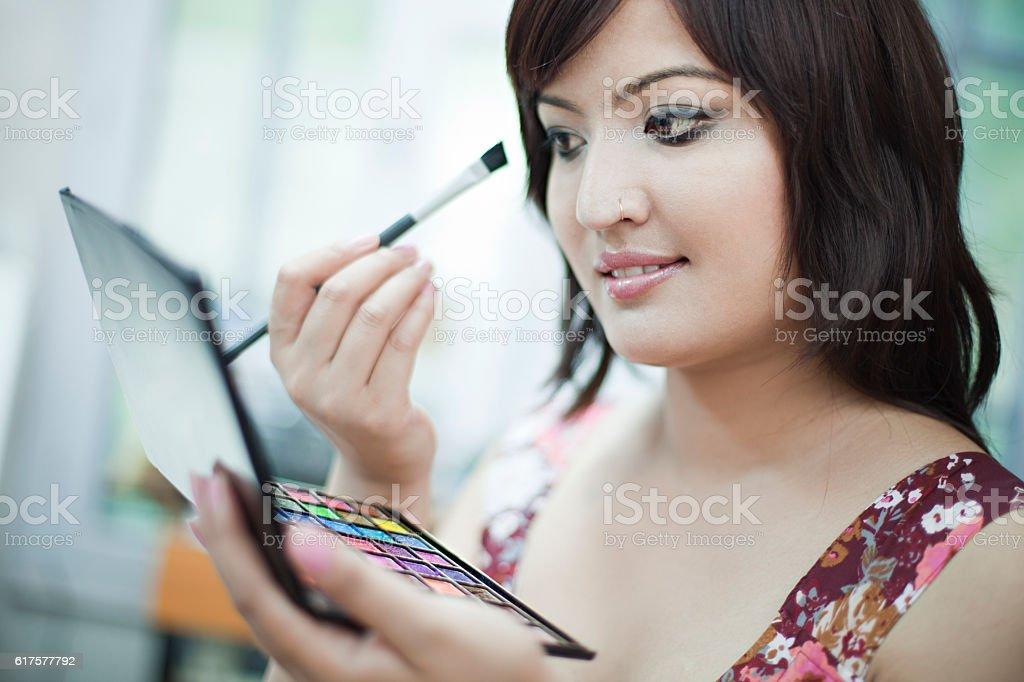 Beautiful Asian woman doing makeup while looking at mirror. stock photo