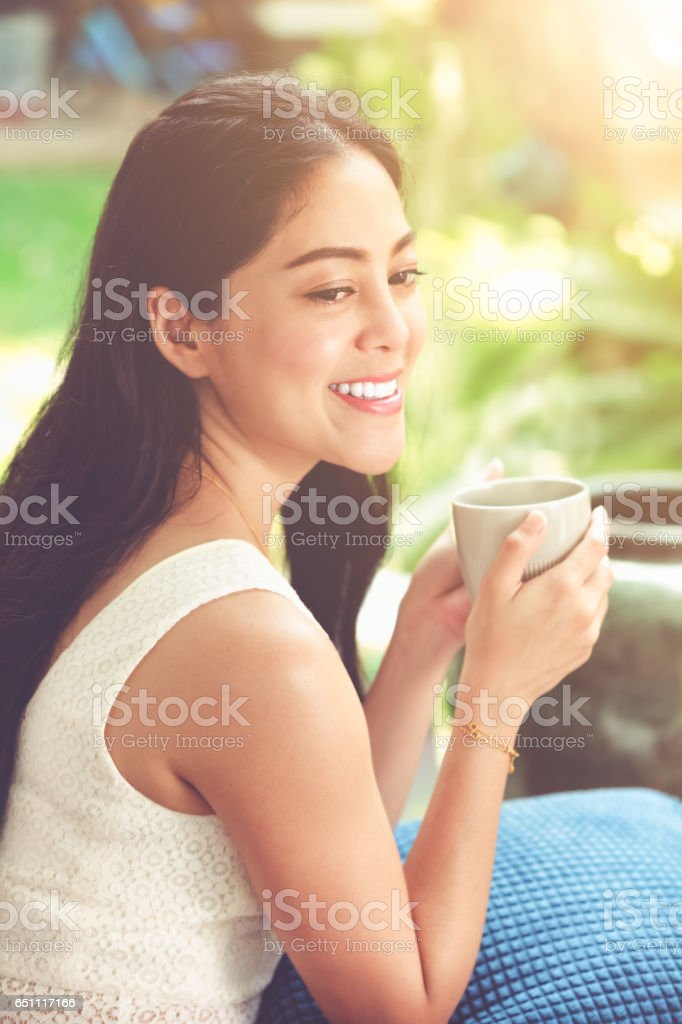 Beautiful asian woman enjoys fresh coffee in the morning. stock photo