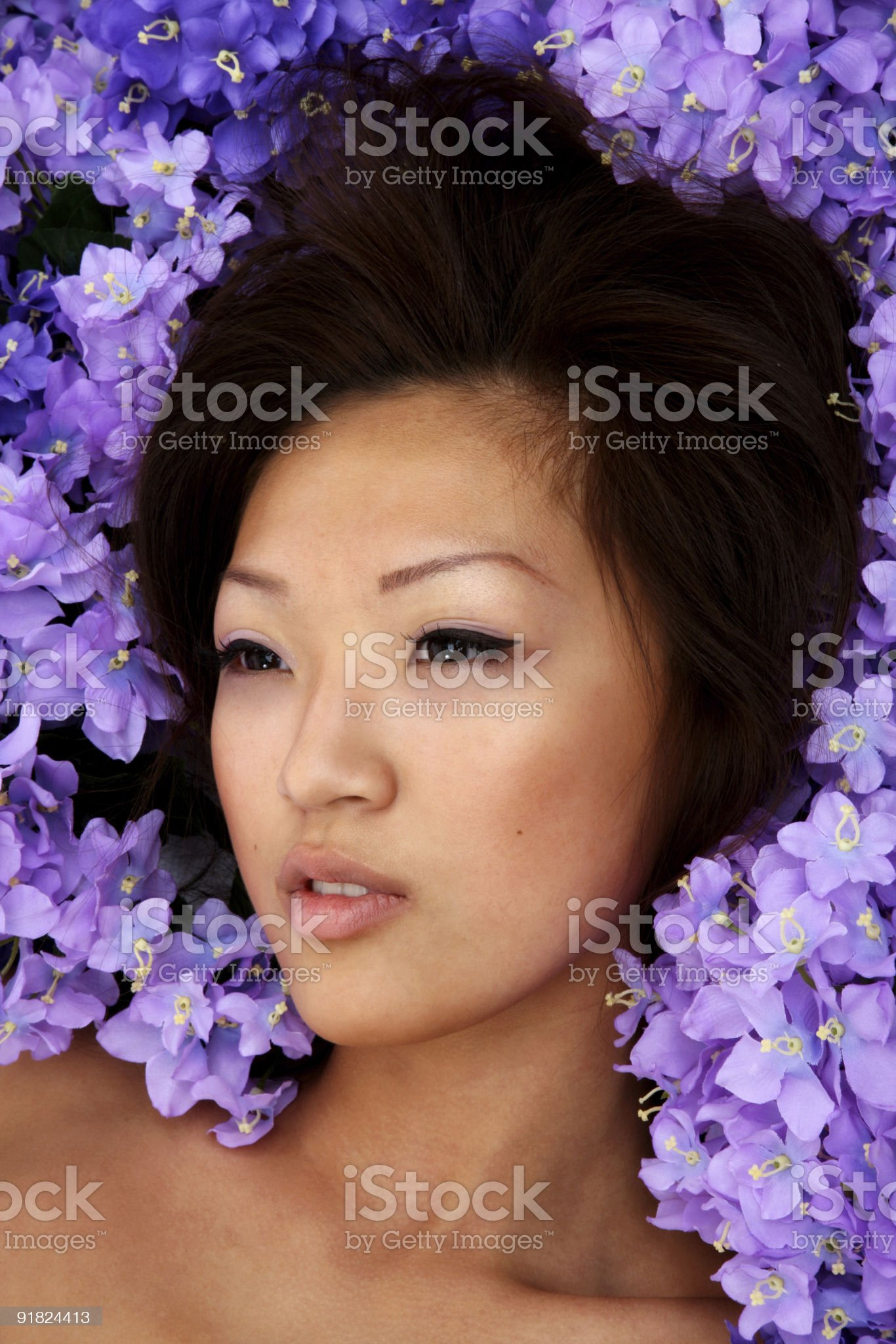 Beautiful Asian woman headshot laying in flowers royalty-free stock photo
