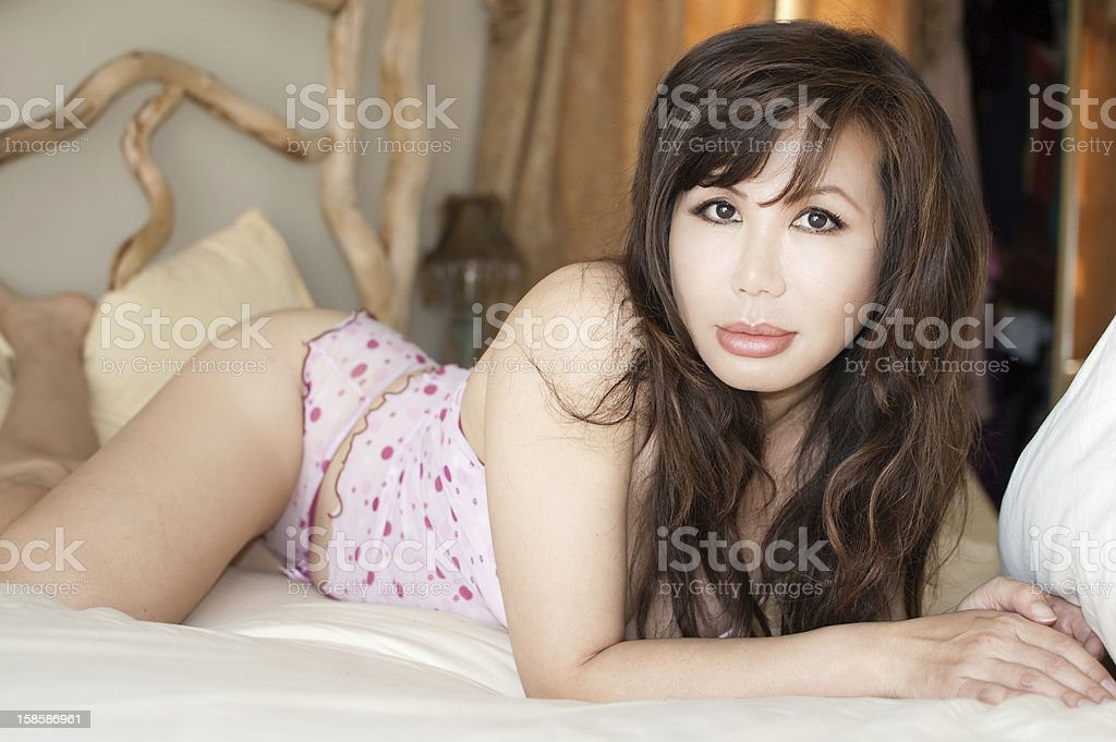 Beautiful Asian Woman lies on bed royalty-free stock photo