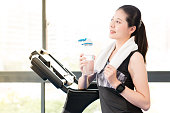 Beautiful asian woman rest holding water bottle after treadmill