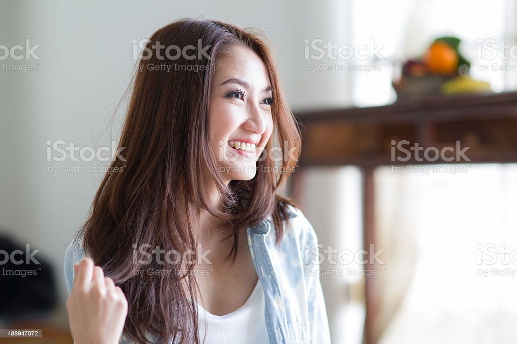 Beautiful asian woman sitting among morning sunshine stock photo