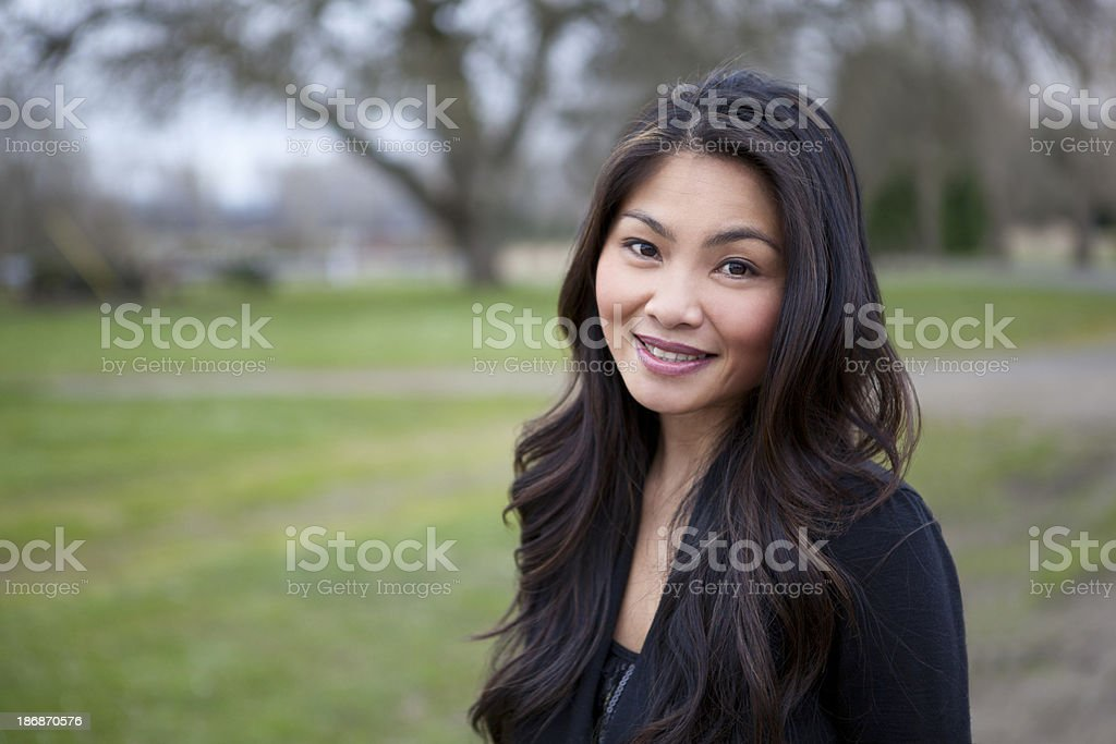 Beautiful Asian woman smiles in a field stock photo