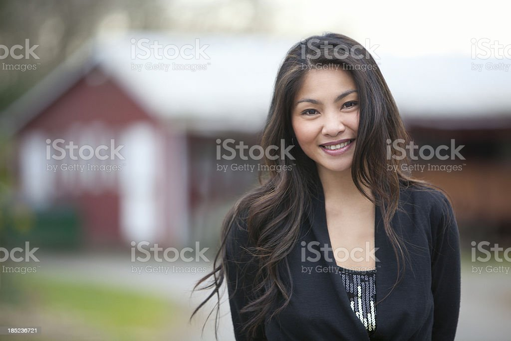 Beautiful Asian woman smiles near a barn. stock photo