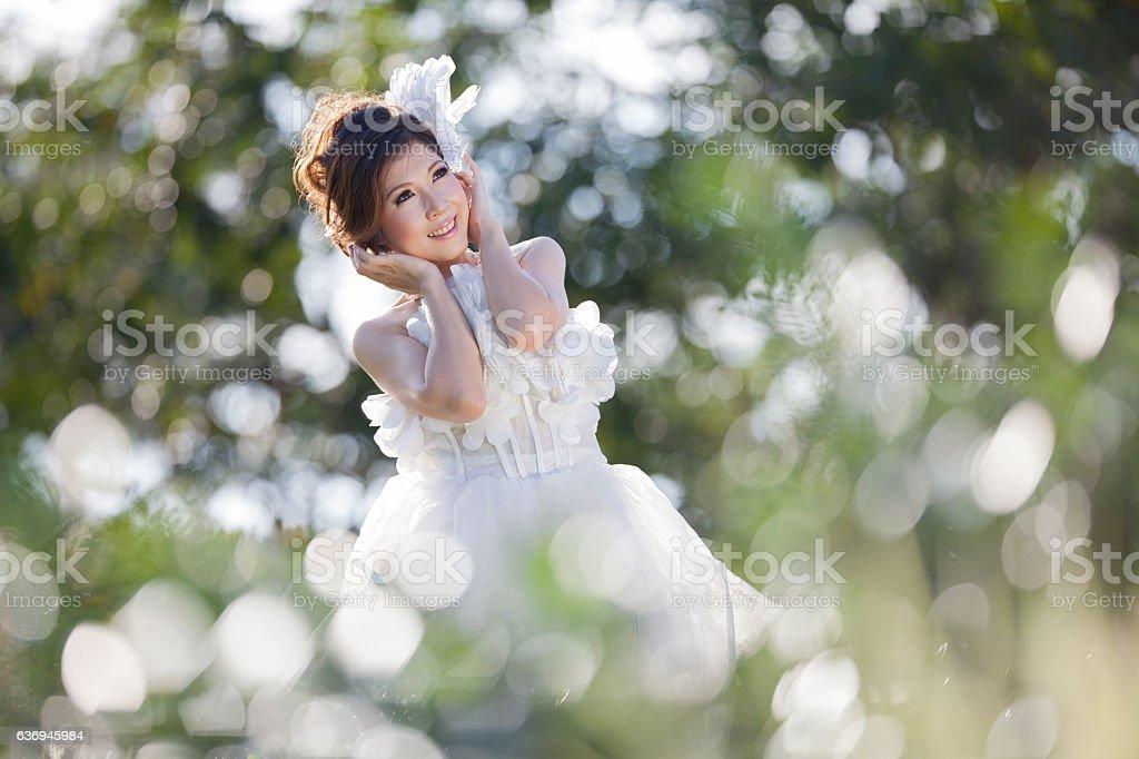 beautiful asian woman  white dress bride in forest sunshine dayl stock photo