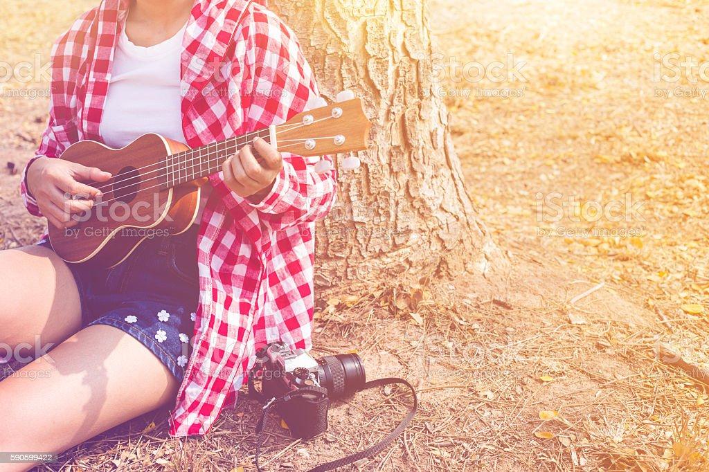 Beautiful asian women playing ukulele guitar at outdoor stock photo