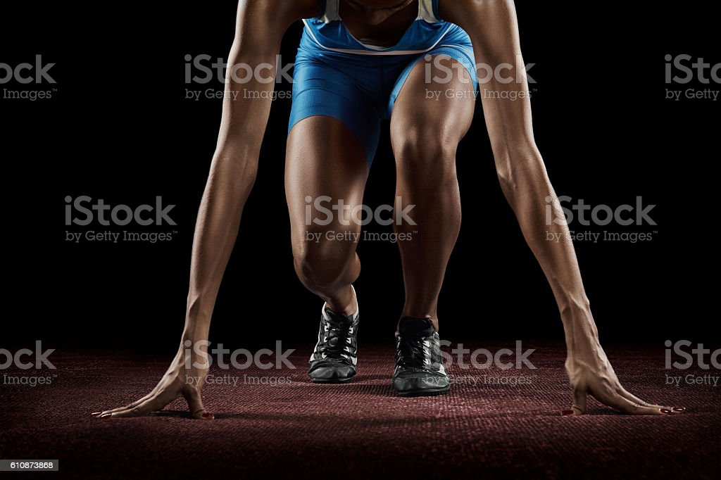 Beautiful athlete on a race track is ready to run stock photo