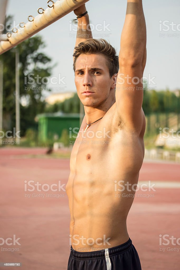 Beautiful athlete relaxing while doing pull ups. Muscular upper stock photo