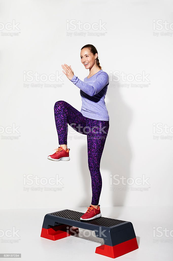Beautiful athlete stepping on gym step, studio stock photo