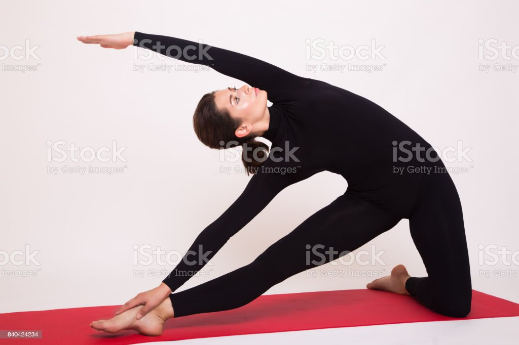 Beautiful athletic girl in black suit doing yoga asanas. Isolated on white background. stock photo