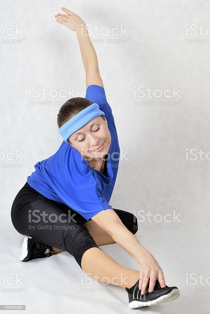 Beautiful athletic girl pulls the leg muscles stock photo