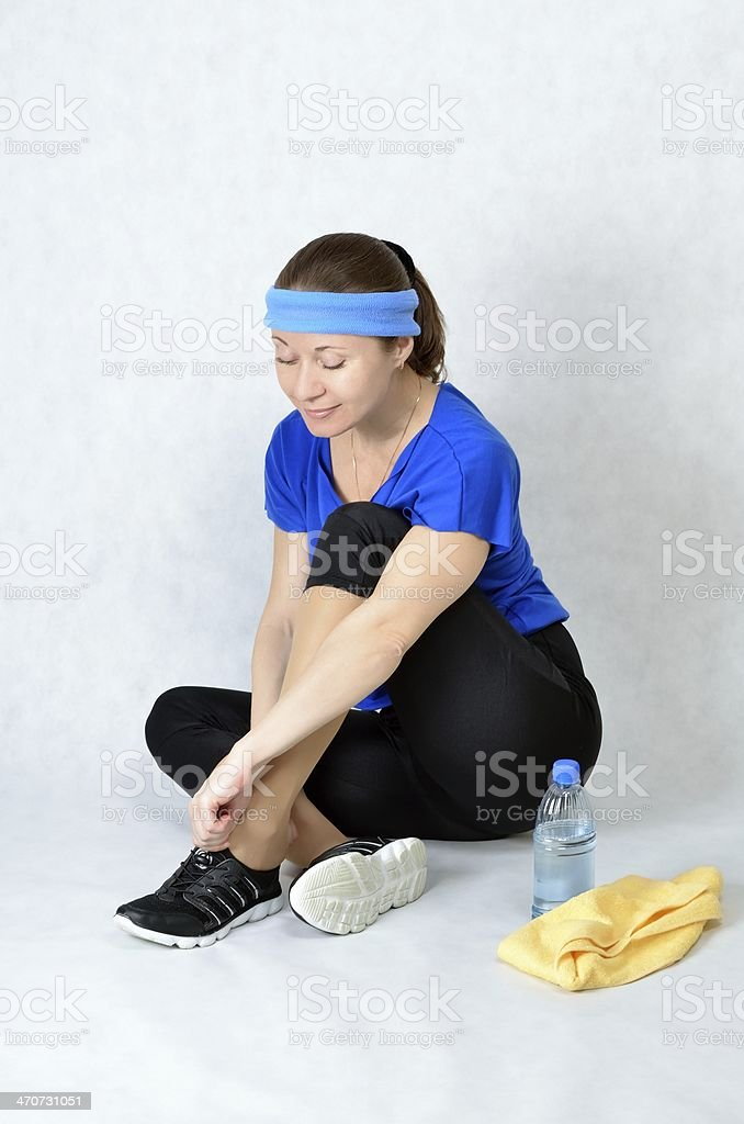 Beautiful athletic girl sitting on the floor resting stock photo