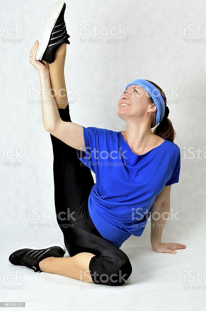 Beautiful athletic woman stretches stock photo