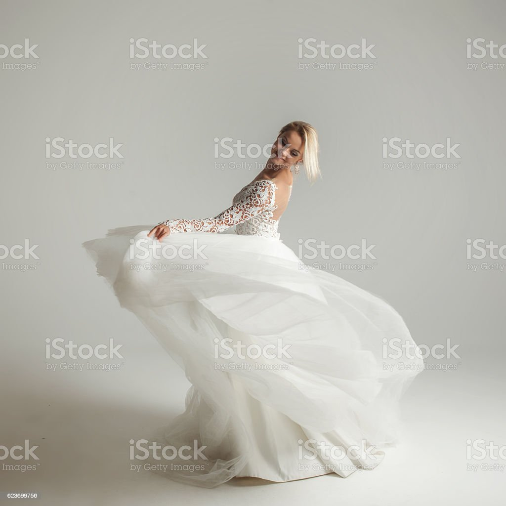Beautiful attractive bride in wedding dress with long full skirt stock photo