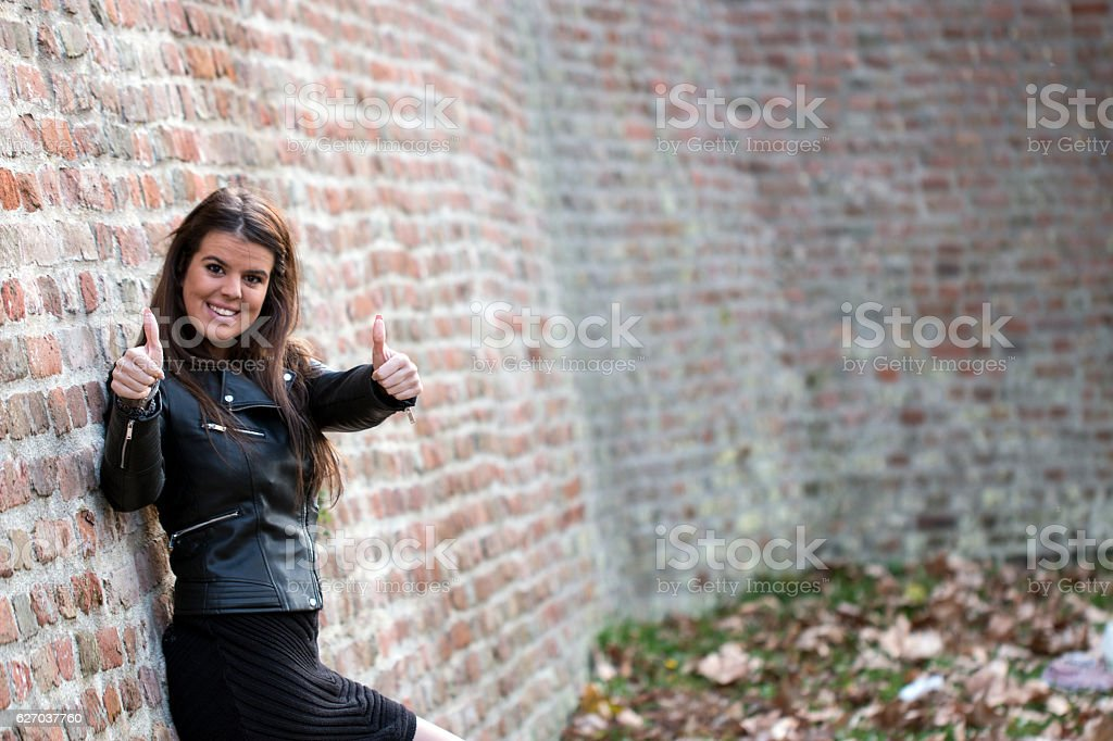Beautiful attractive girl shows two thumbs up stock photo