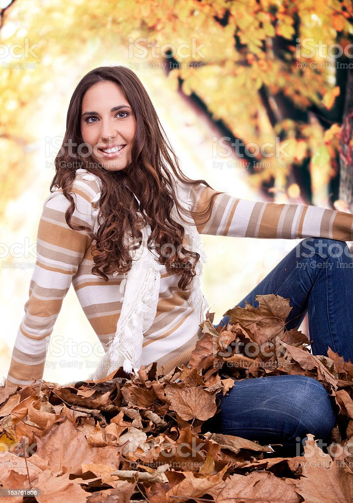 beautiful autumn woman sitting on leaves outdoor royalty-free stock photo