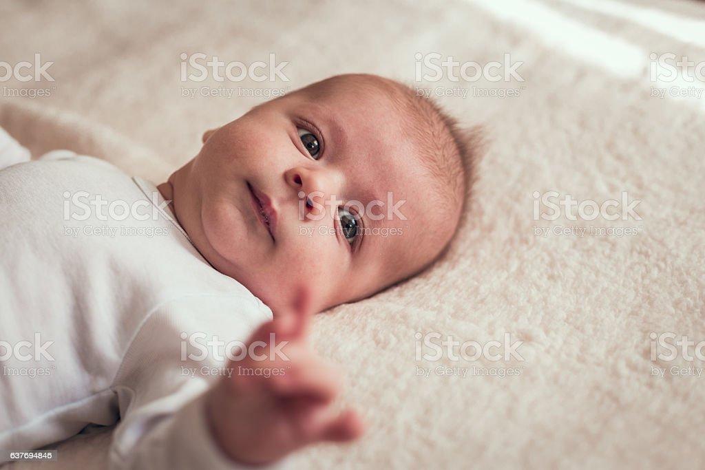 Beautiful baby boy lying on the white blanket stock photo