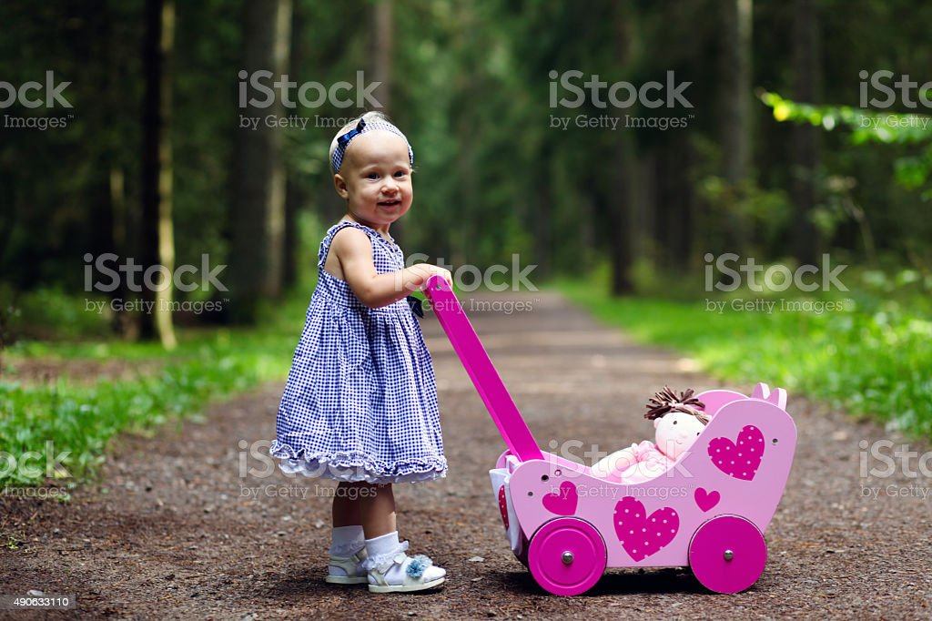 Beautiful baby girl and her doll buggy stock photo