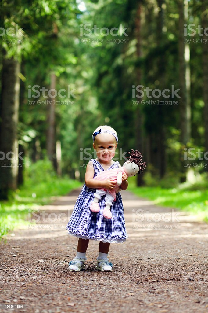 Beautiful baby girl and her doll stock photo