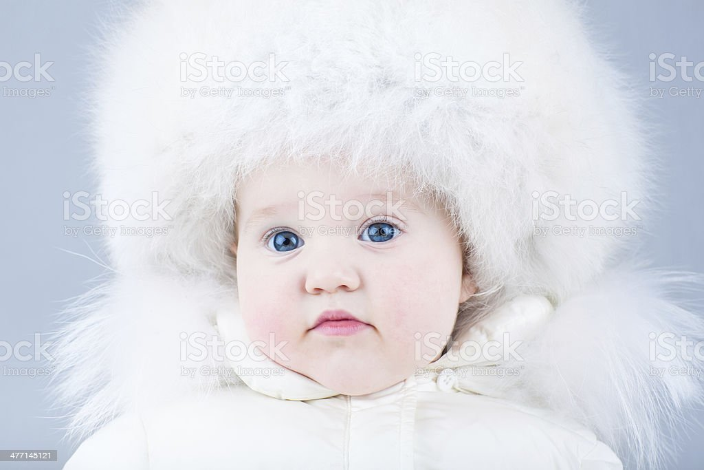 Beautiful baby girl in a white winter jacket royalty-free stock photo