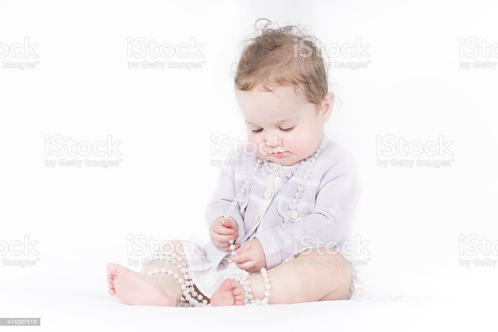 Beautiful baby girl playing with pearls royalty-free stock photo