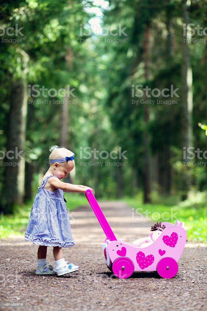 Beautiful baby girl pushes her doll pram stock photo