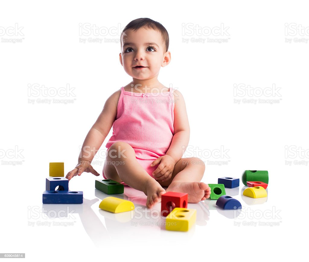 Beautiful baby girl sitting with toy blocks and smiling stock photo