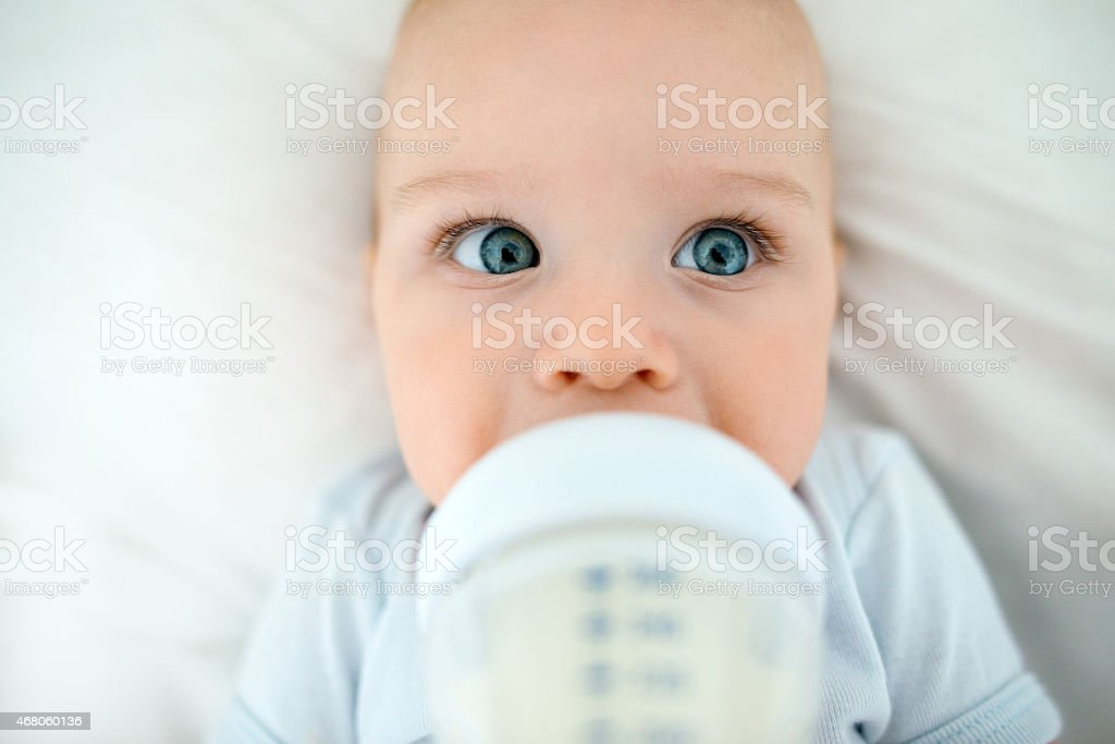 beautiful baby lying on his back in bed drinking milk stock photo