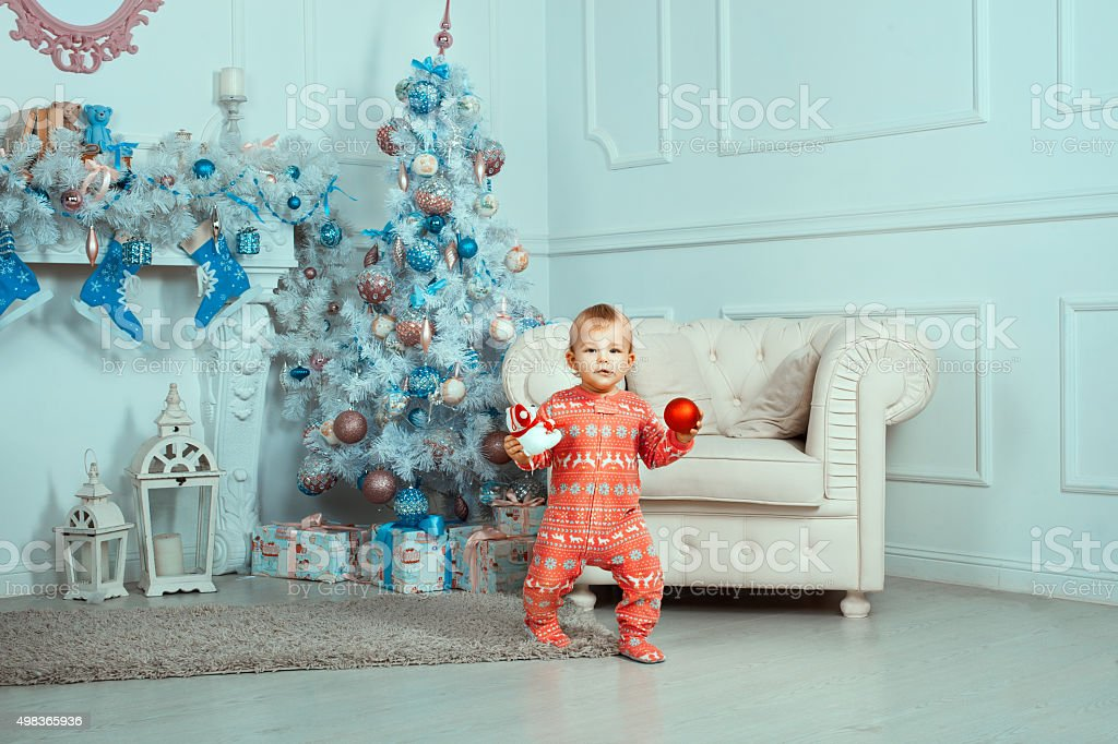 Beautiful baby near Christmas tree stock photo