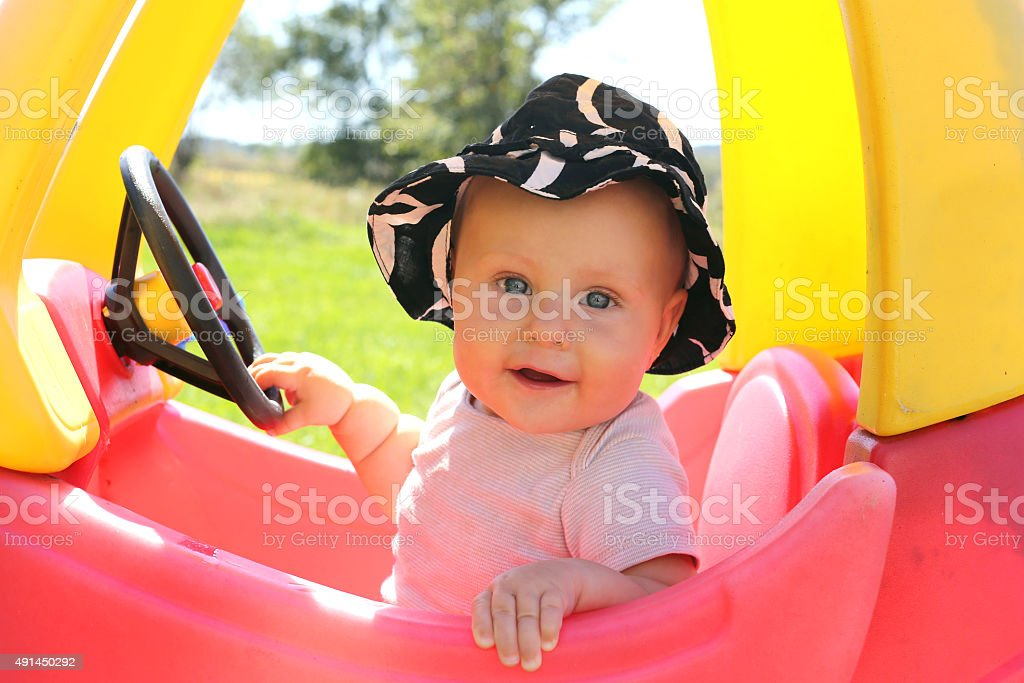 Beautiful Baby PLaying Outside in Toy Car stock photo