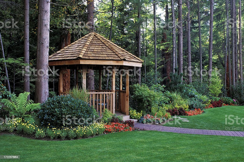 A beautiful backyard garden with a cedar wood gazebo stock photo