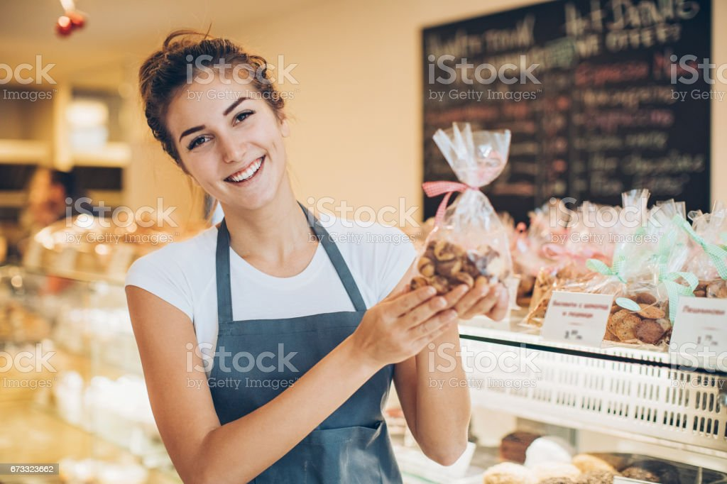 Beautiful baker holding a cookies package stock photo