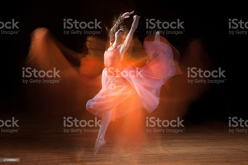 Beautiful Ballerina Dancing on Dark Stage with Ghosts stock photo