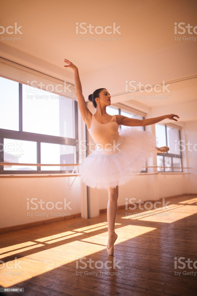 Beautiful ballerina dancing standing on one leg stock photo