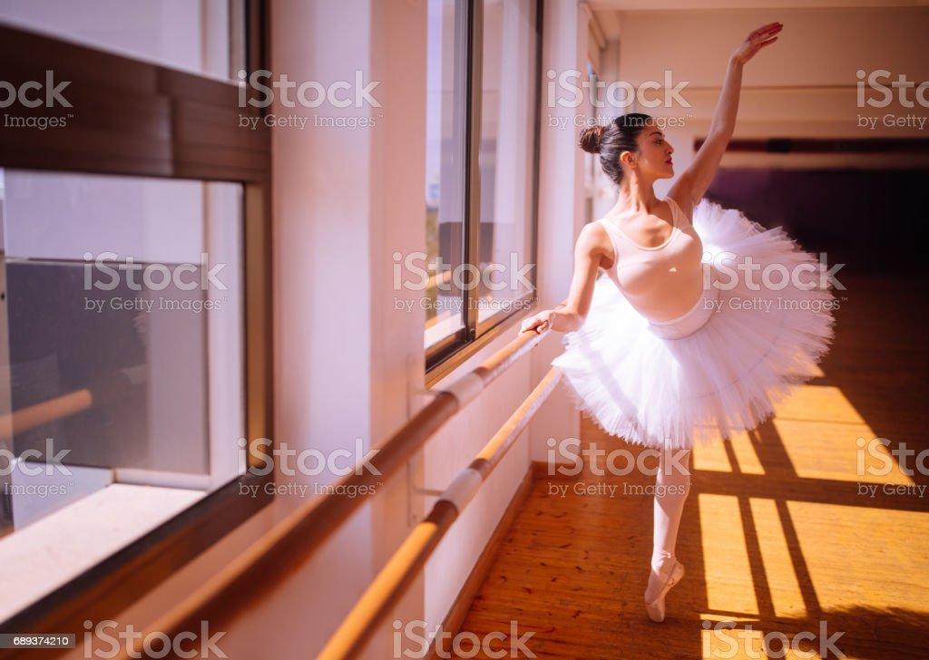 Beautiful ballerina showing her techniques in a ballet studio stock photo