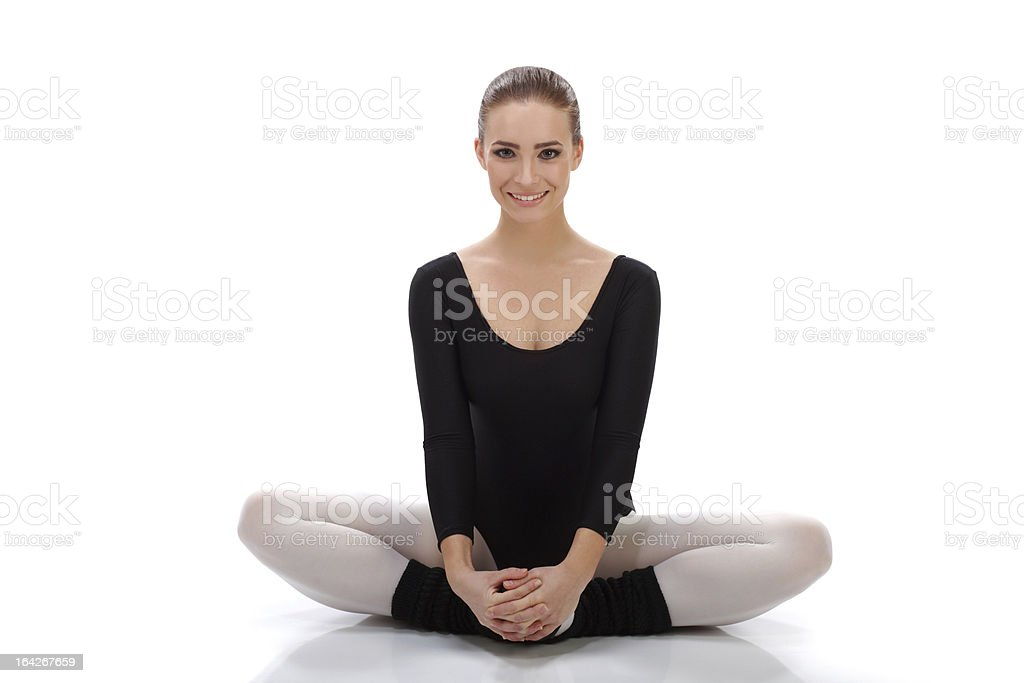 Beautiful ballerina smiling and stretching before practice royalty-free stock photo