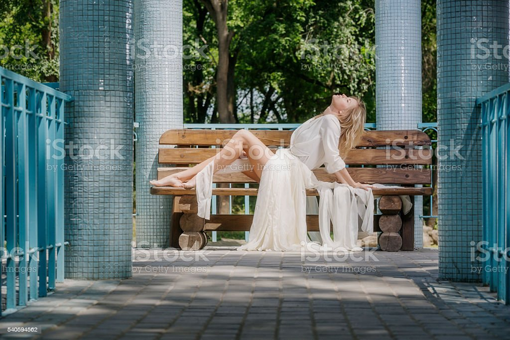 Beautiful barefoot blond woman resting on bench in gazebo stock photo