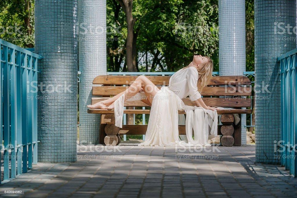 Beautiful barefoot blond woman resting on bench in gazebo stock photo