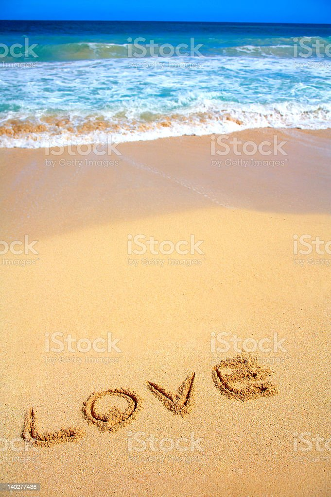 Beautiful beach in Hawaii with 'LOVE' scratched into the sand royalty-free stock photo