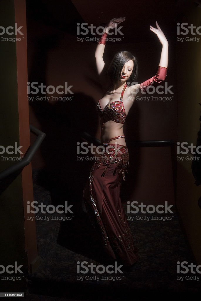 Beautiful belly dancer in a dark red room stock photo