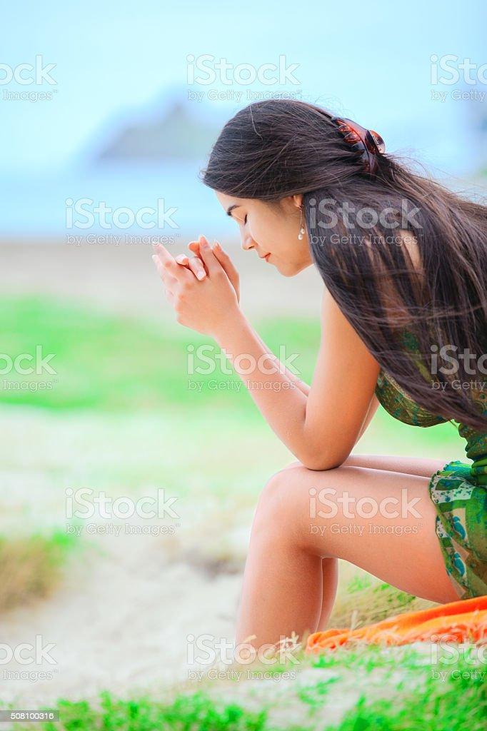 Beautiful biracial teen girl sitting at tropical beach, praying stock photo