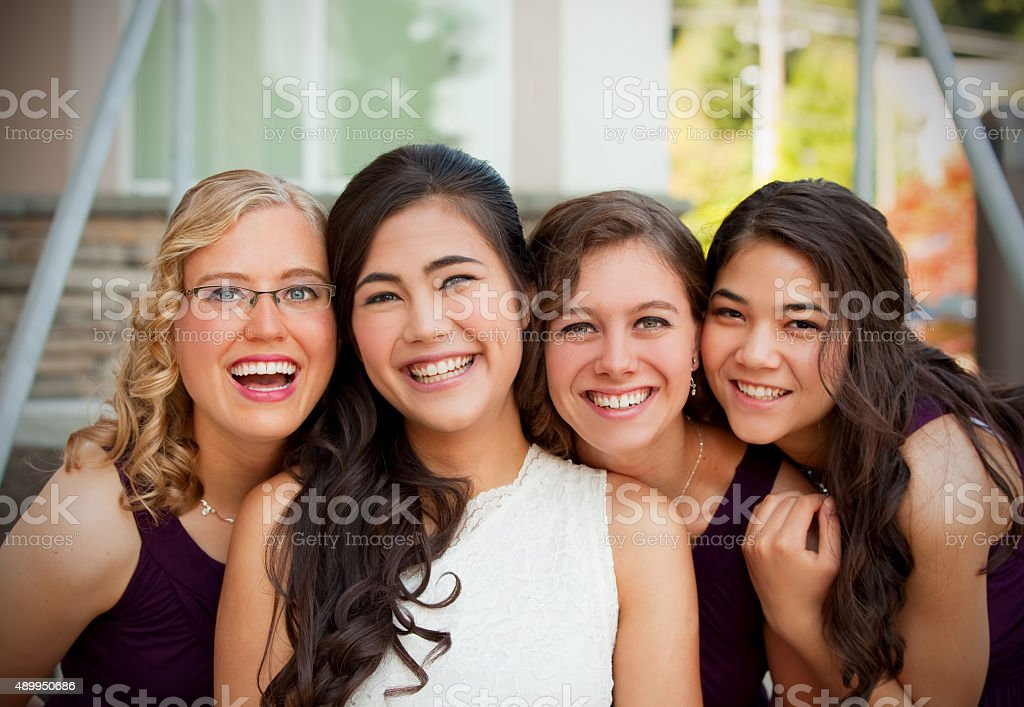 Beautiful biracial young bride smiling with her  bridesmaids stock photo